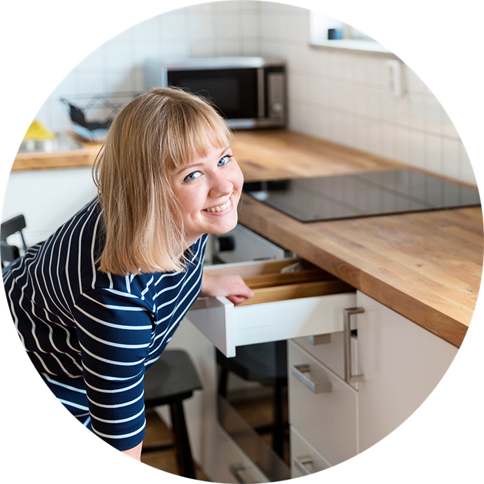 a woman pulling out a drawer in a kitchen